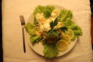 Салат с кальмарами. Ингредиенты: кальмар, пассированный лук, вареное яйцо, листья салата, лимон, майонез